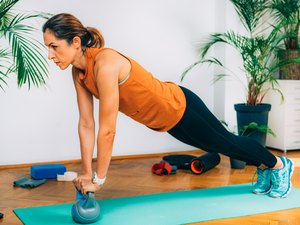 woman doing a plank kettlebell exercise on a teal yoga mat at home