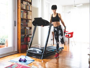 Woman stretching before using treadmill machine for a home cardio workout