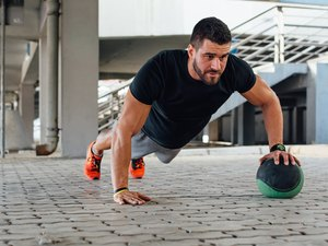 man performing push ups with medicine ball outside