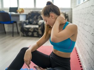 Woman experiencing neck pain during her workout.
