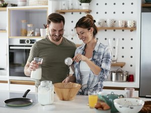 Young couple making pancakes at home