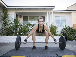 Woman doing dead lifts with weights at home