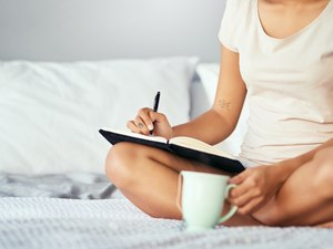 A woman sitting in bed drinking coffee and writing down her bathroom habits to track her gut health