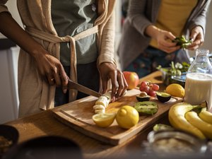 Female hands cooking and prepping plant based foods in kitchen