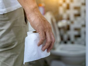 Man holding toilet tissue roll in bathroom looking at loo