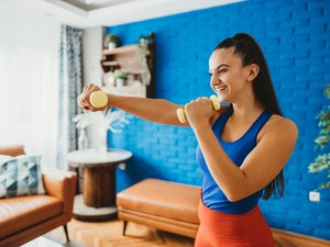woman holding a pair of dumbbells and doing a standing ab workout at home
