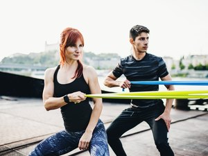 Fit man and woman exercising with resistance bands outdoors