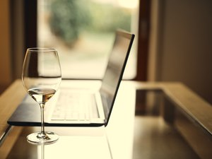 close up of a wine glass next to a laptop on a glass table