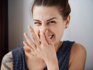 A woman holding her nose because her farts smell really bad