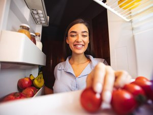 Young woman taking fresh healthy vegetables from fridge