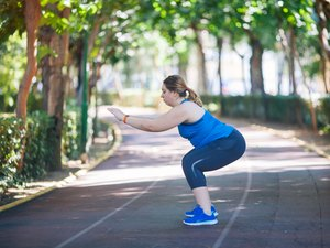 Woman doing a squat workout in park