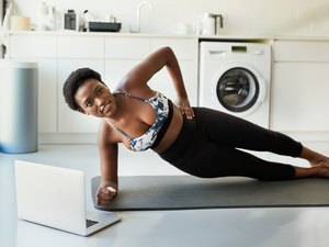 Woman doing a side plank during an ab workout at home with her laptop