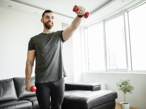 fit man doing a light dumbbell arm workout in his living room with a pair of red dumbbells