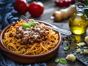 Spaghetti with Bolognese sauce shot on rustic wooden table