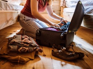 Unrecognizable woman packing luggage in log cabin