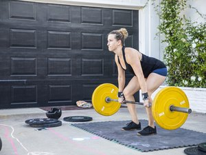 woman doing deadlifts with a barbell outside of her home