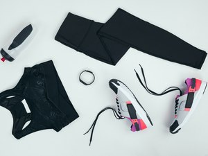overhead shot of workout gear, including black leggings, sports bra, sneakers, water bottle and smartwatch