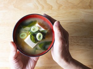 overhead photo of hands holding red and black bowl of miso soup