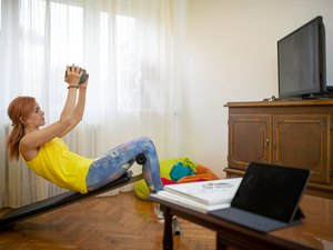 woman doing sit-ups on an exercise bench in her living room
