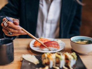Man's hand showing man eating sushi in sushi bar