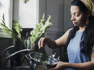 Woman washing food in colander standing at kitchen sink