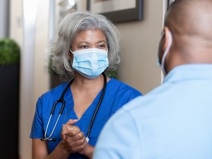 woman doctor discussing cholesterol levels with male patient wearing face masks