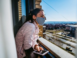 Woman in a mask checking the window to see if the room is well ventilated