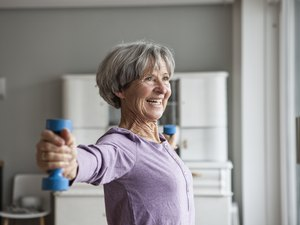 senior woman wearing a purple sweater and lifting blue dumbbells at home