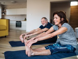 older adults doing low-impact exercises on mats on the floor at home
