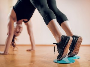 woman doing a pike plank using the best exercise sliders for home workouts
