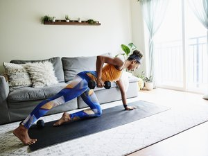 Woman working out with dumbbell in living room of home, doing dumbbell back exercises