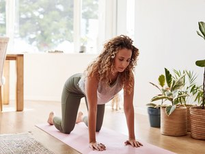 Woman setting up to do a bear plank in her living room surrounded by plants