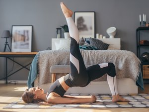 woman wearing white color-blocking leggings and doing a single-leg glute bridge in her bedroom