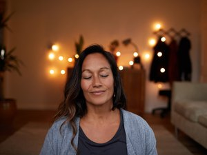 Serene mature woman smiling while meditating at home