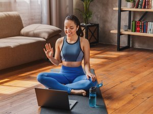 woman sitting down on a black yoga mat and waving at a laptop t in her living room