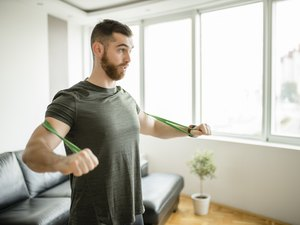 Sporty man  doing exercises with resistance band at home