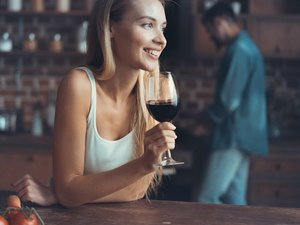 woman drinking some wine at home in kitchen .