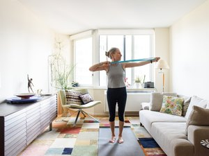 woman over 60 doing a resistance band workout in her living room