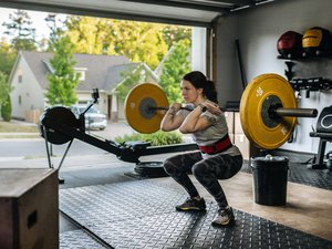 woman performing front squat with the best weight lifting equipment in home gym in garage