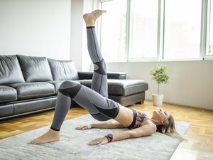 woman wearing color-blocking leggings and doing a single-leg glute bridge exercise in her living room