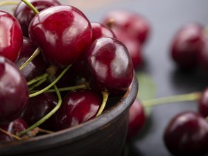 Freshly harvested cherries in a clay bowl from your home garden.