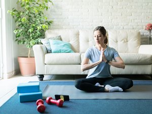 woman working out with a yoga block and dumbbells in her living room