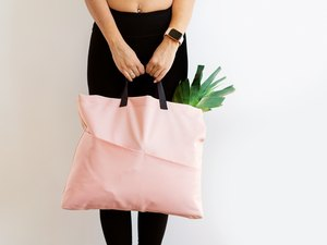 Fit woman holding a heavy pink bag full of groceries