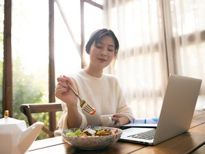 Young woman eating lunch while working with laptop