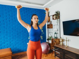 woman wearing bright blue tank and orange leggings doing a shoulder dropset dumbbell workout at home