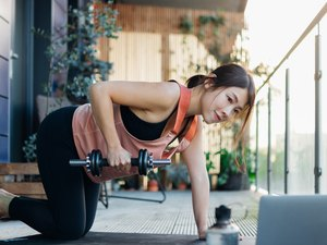 fit Asian woman doing a dumbbell row with adjustable dumbbells on her balcony