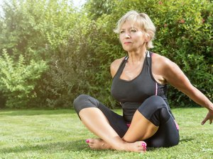 Senior woman is sitting in a stretched pose outdoors, trying to grab her hands behind her back