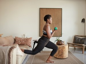 Black woman doing a low-impact strength training workout with dumbbells in he rliving room