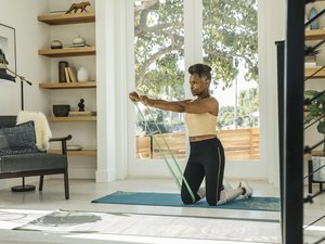 black woman working out her obliques with a green long-looped resistance band in her living room