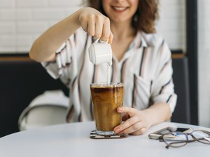 woman Pouring cream in cold brew coffee